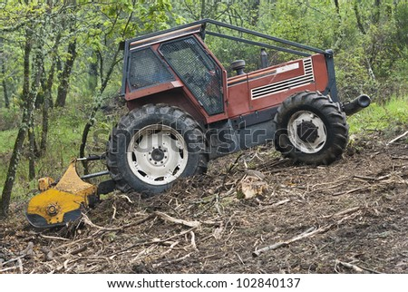 tractor forest clearing in the woods with a brush-cutter