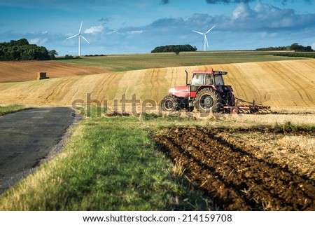 Tractor harrowing a field west of Poitiers in south western France, Europe - stock photo