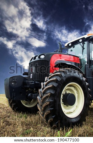 tractor harvesting a wheat field - stock photo