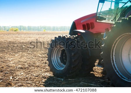 Tractor in a field in autumn on a bright sunny day