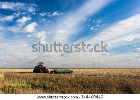 Tractor in Field with Blue Streaky Sky - stock photo