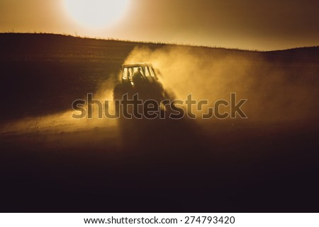 Tractor in sunset plowing the field - stock photo
