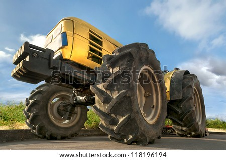 Tractor in the field with a blue sky - stock photo