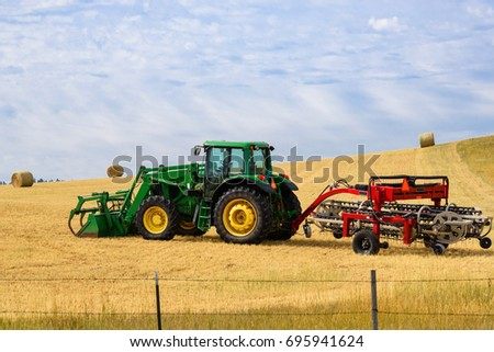 Tractor in the field with a rake attached. Raking hay. Blue sky background.