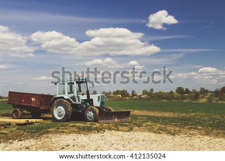 Tractor in the field with blue sky and clouds - stock photo