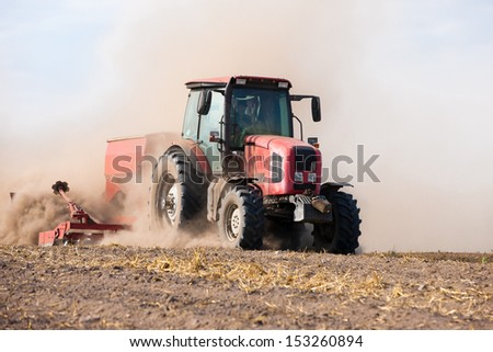Tractor machine Cultivation field during agricultural works - stock photo