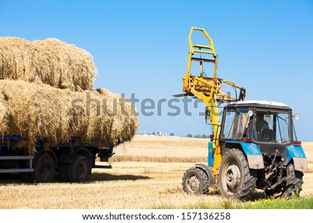 Tractor machine loading hay bales on truck trailer during agriculture works - stock photo