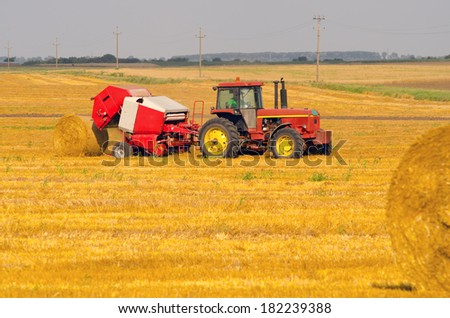 Tractor making hay bales on sunny summer day. - stock photo