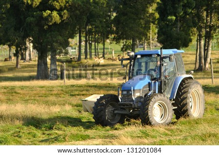 Tractor mowing pasture for silage, West Coast, South Island, New Zealand - stock photo