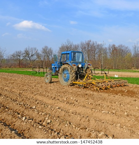 Tractor on a spring field - stock photo