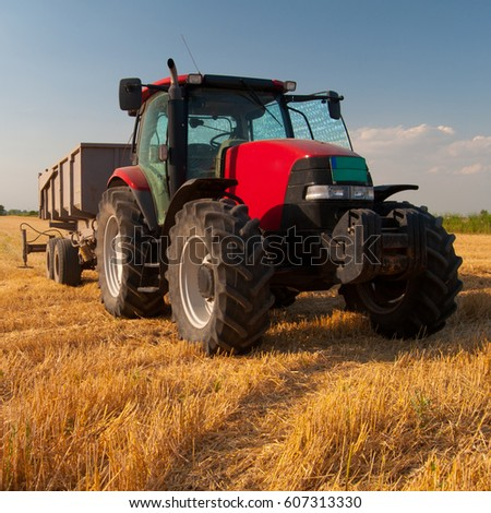 Tractor on agricultural field after summer harvest.