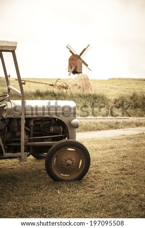 Tractor on field, windmill in background, Bornholm, Denmark - stock photo