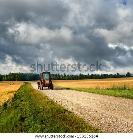 tractor on the road and cereal field against dark stormy clouds - stock photo