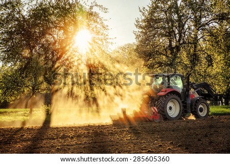 Tractor plowing a field at sunset in beautiful sunlight falling through trees and dust with light and shadow effects, no logos or faces - stock photo