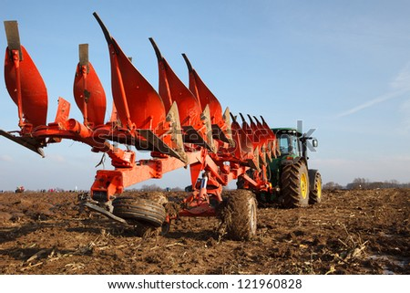 Tractor plowing field in sunny autumn day - stock photo