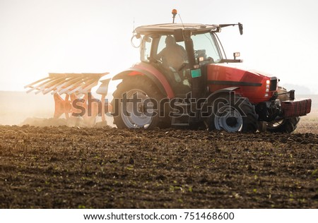 Tractor plowing fields -preparing land for sowing