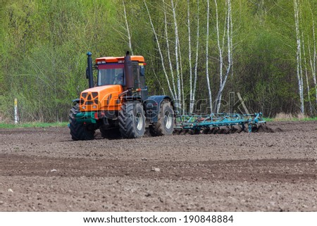 Tractor plowing the field in the spring