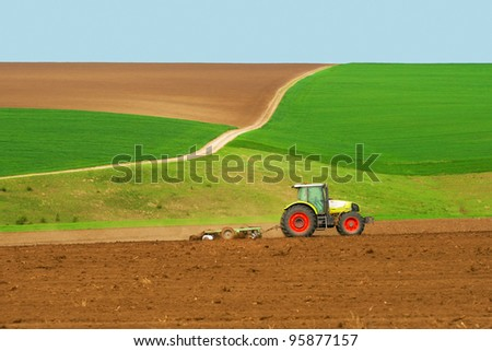 Tractor plowing the fields green with blue sky