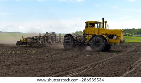 tractor plowing the land - stock photo