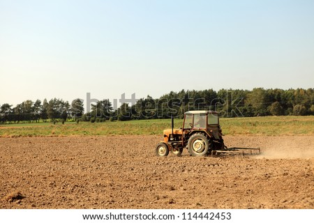 tractor plowing the soil in the farmland showing scraper