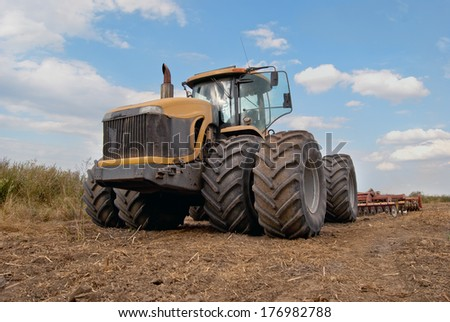 tractor plows a field in the spring - stock photo