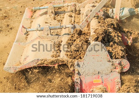 Tractor plows a field shoveling - stock photo