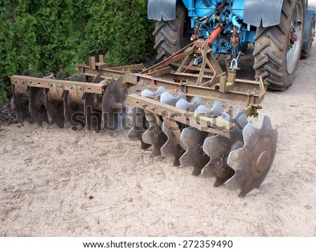 Tractor powered heavy disc harrows on ground - stock photo