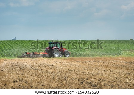 Tractor preparation the stubble field - stock photo