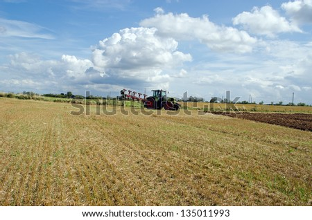 tractor prepared for plow stand near agricultural harvested field.