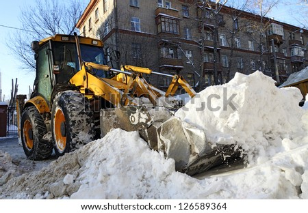 Tractor removes snow on city street - stock photo