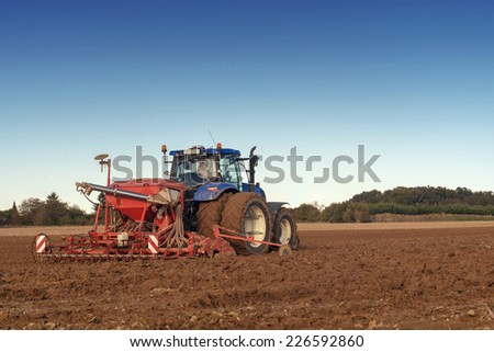 tractor seeding in a field on blue sky background - stock photo