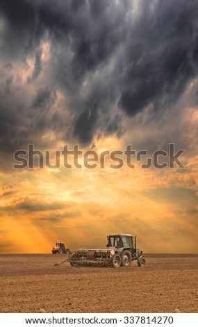 Tractor seeding the field on stormy sunset - stock photo