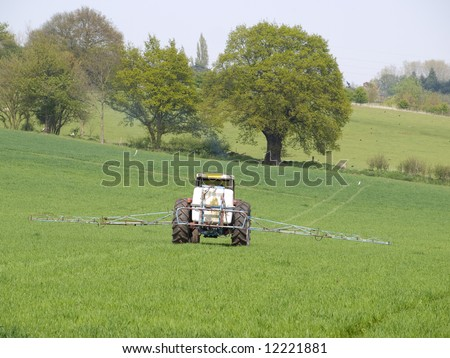 Tractor spraying crops in a field - stock photo