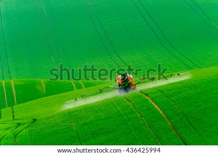 Tractor spraying the chemicals on the green field - stock photo