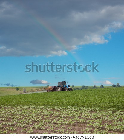 Tractor spraying the field with a rainbow over the horizon