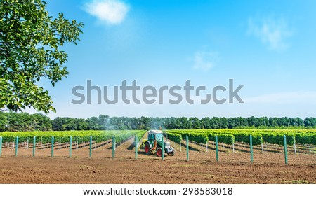 Tractor spraying with sprayer, herbicides and pesticides. - stock photo