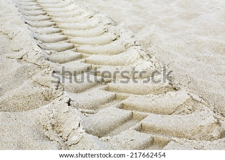 Tractor tires footprint on a sandy beach - stock photo