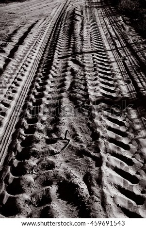 Tractor tracks on a sandy path.