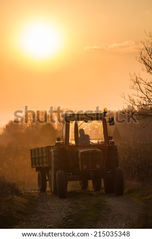 Tractor-trailer approaching from a dirt road to sunset - stock photo