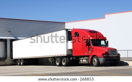Tractor trailer sitting at a loading dock.  Space for text on the trailer. - stock photo