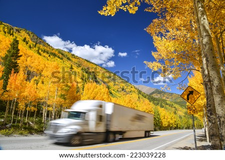 tractor trailer truck driving along Colorado highway on colorful autumn day - stock photo