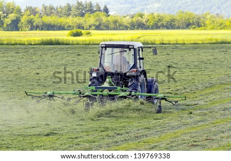 Tractor turning cut hay in a field.