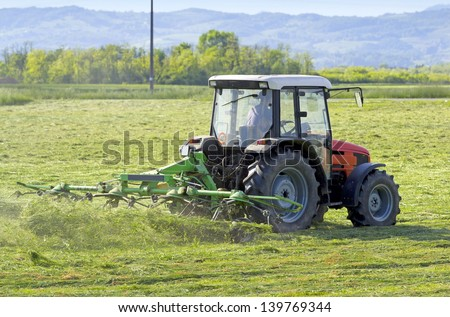 Tractor turning cut hay in a field. - stock photo