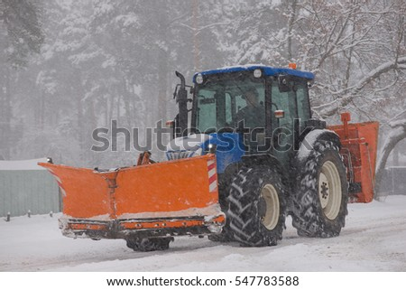 tractor with a snow shovel driven down the street