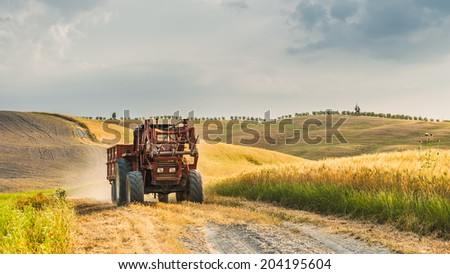 Tractor with a trailer on the fields in Tuscany, Italy - stock photo