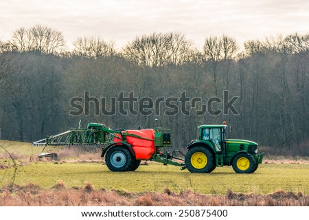 Tractor with ferilizer on a field in early spring - stock photo