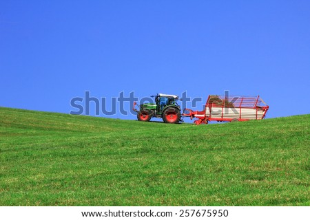 tractor with hay rack, harvesting animal forage - stock photo