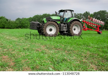 tractor with plows on the field - stock photo