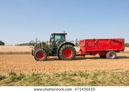 Tractor with red trailer carrying grain