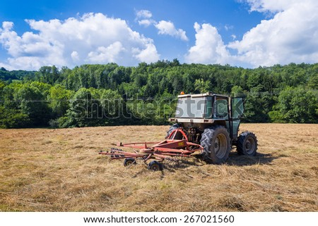 Tractor with rotary rakes parked on dry grassland in Cazavet France - stock photo